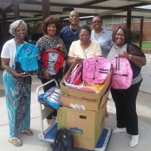 Donating school supplies to local school.